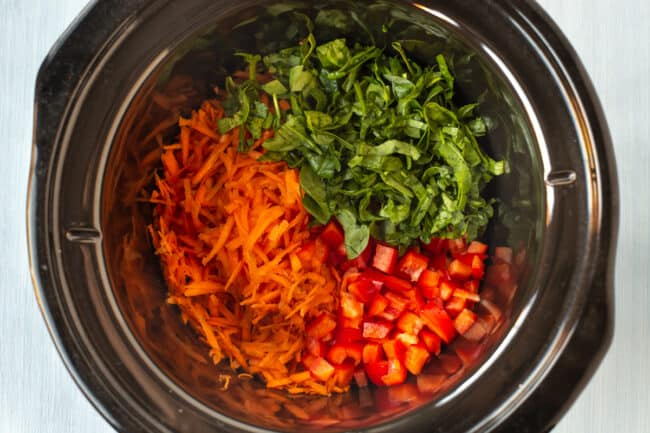 Grated carrot, spinach and red pepper in a slow cooker.