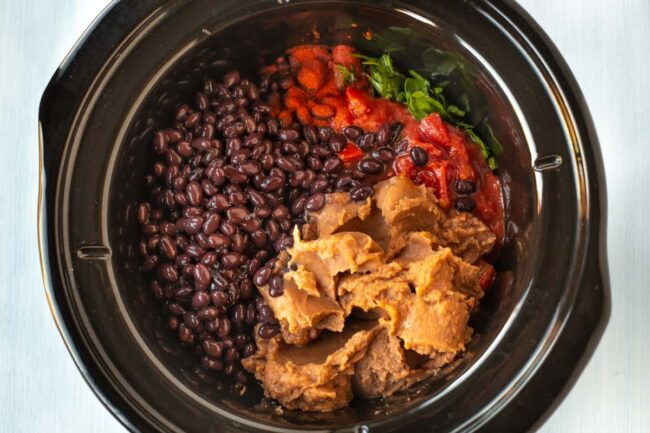 Black beans, chopped tomatoes and refried beans in a slow cooker.
