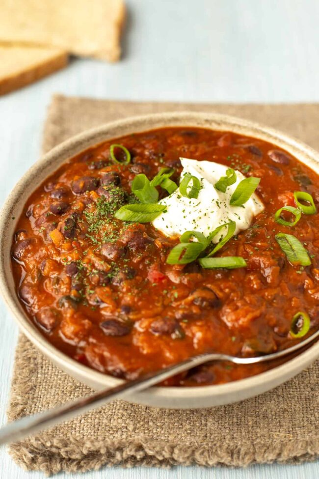A bowlful of black bean soup topped with spring onions and sour cream.