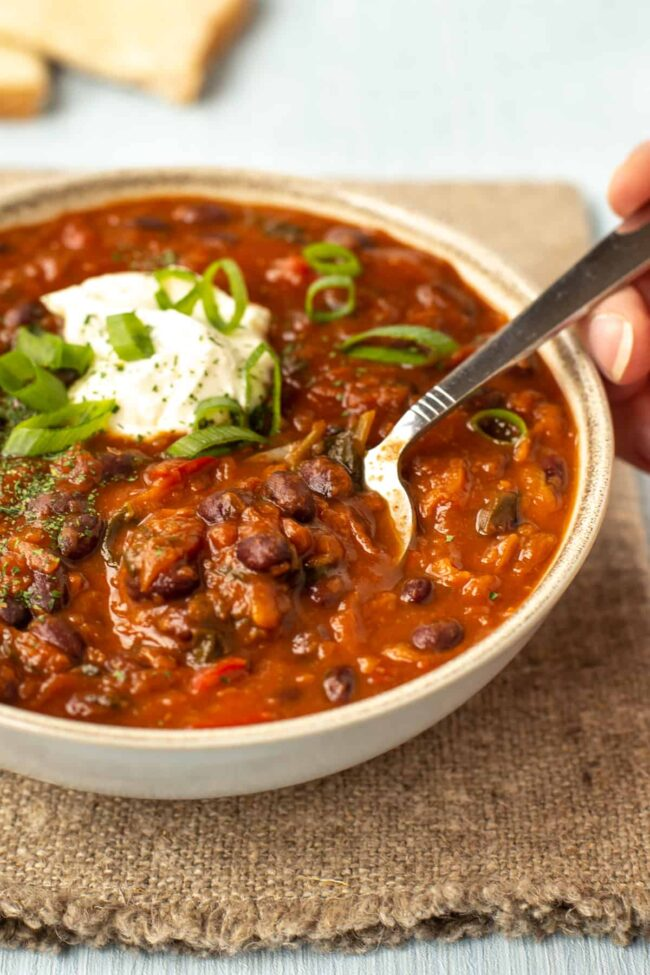 A spoon taking a scoop from a bowlful of black bean soup.