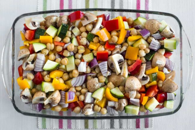 Chopped vegetables and chickpeas in a baking dish ready to make ratatouille