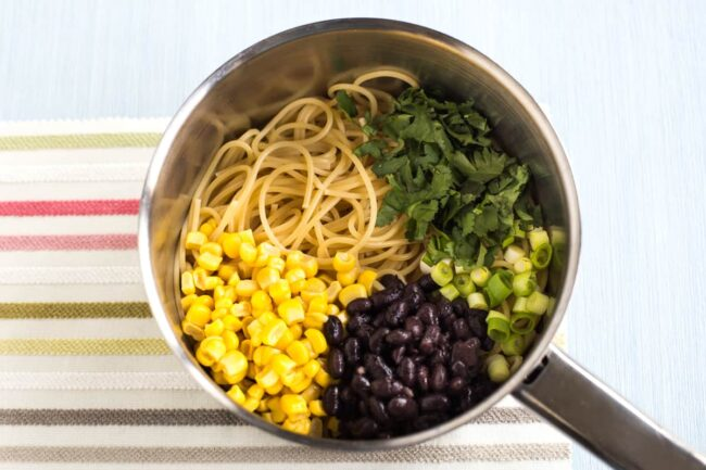 Spaghetti in a saucepan topped with sweetcorn, black beans, spring onions and cilantro