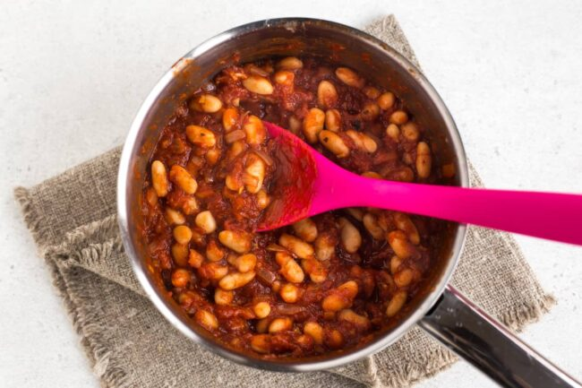 Homemade vegetarian baked beans cooking in a saucepan.