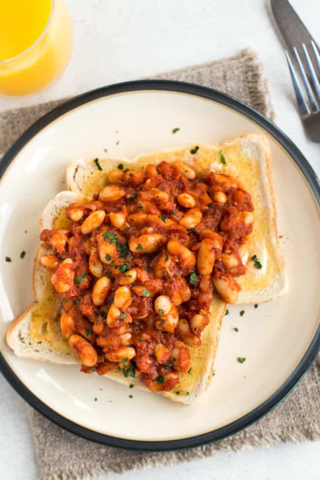Homemade vegan baked beans served on two slices of buttered toast.