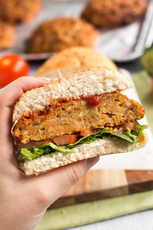 Hand holding up a cheesy lentil burger in a bun, cut in half.