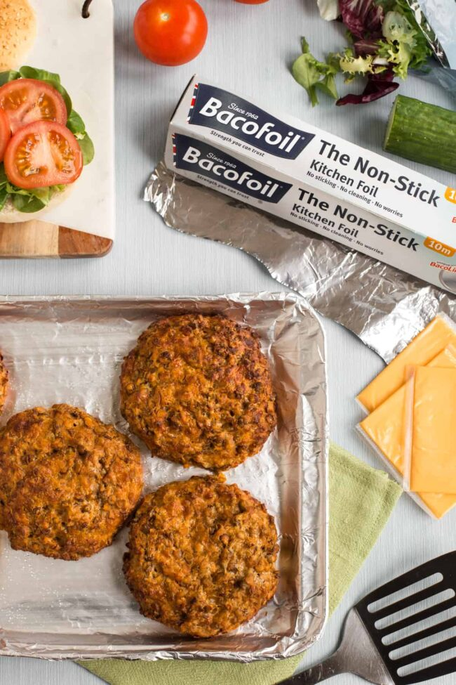 Cheesy lentil burgers on a baking tray, shot from above.