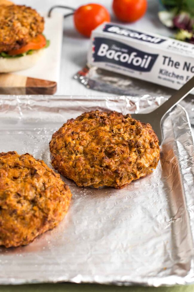 Cheesy lentil burger on a foil-lined baking tray.