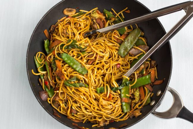 Stir-fried vegetables and noodles in a wok.