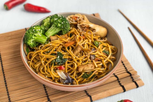 Veggie chow mein in a bowl with a spring roll and steamed broccoli.