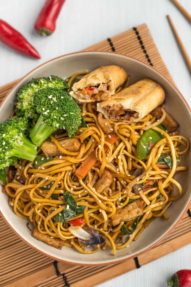 Vegetarian chow mein in a bowl with broccoli and a spring roll.