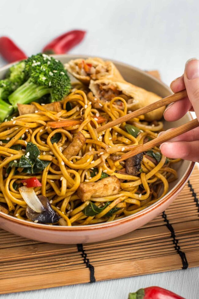 Veggie chow mein being eaten with a pair of chopsticks.