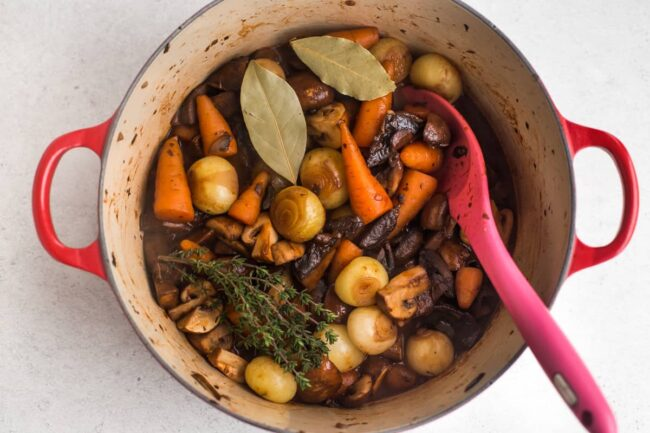Onions, carrots and mushrooms in a large casserole dish with bay leaves and fresh thyme.