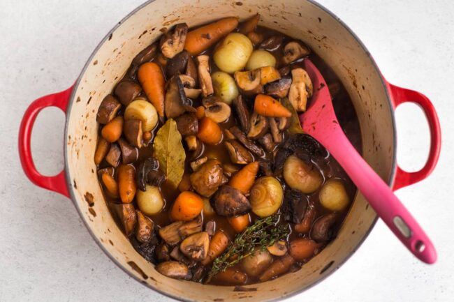 Mushroom bourguignon with carrots and onions in a large casserole dish.