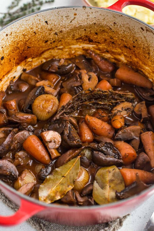 Vegetarian bourguignon in a casserole dish with carrots and onions.