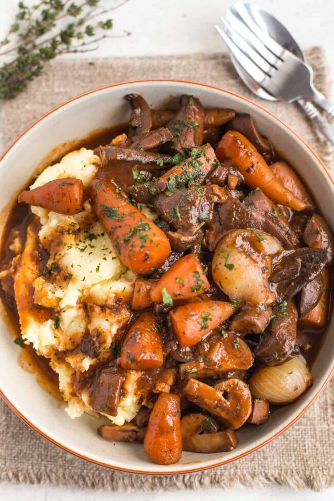 Vegetarian mushroom bourguignon in a bowl with mashed potato.