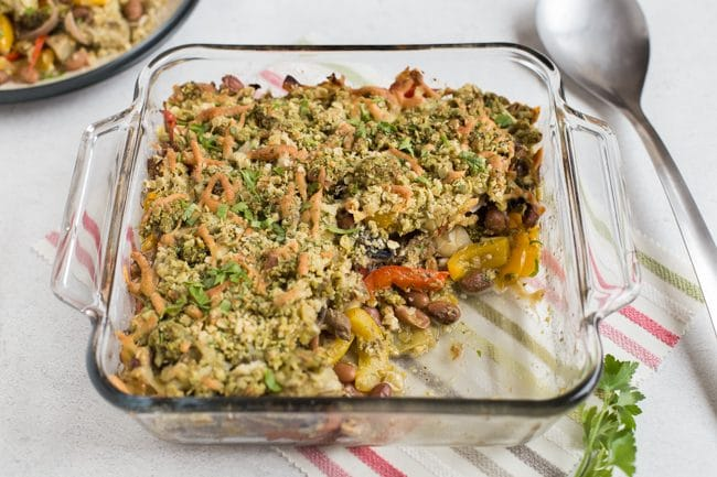 Bean and vegetable crumble in a Pyrex baking dish with a scoop removed