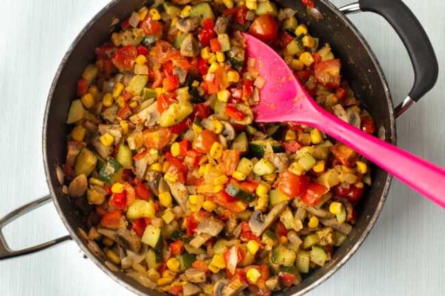 Colourful summer vegetables cooking in a pan.