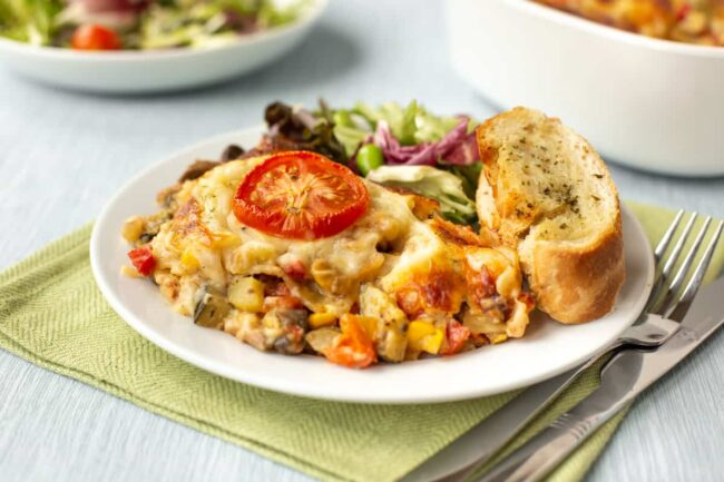 A portion of cheesy vegetarian lasagne on a plate with garlic bread and salad.