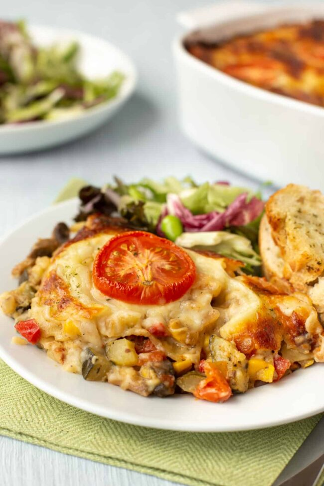 A portion of cheesy vegetable lasagne on a plate with salad and garlic bread.