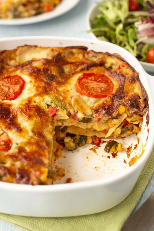 A creamy vegetable lasagne in a dish with a slice removed.