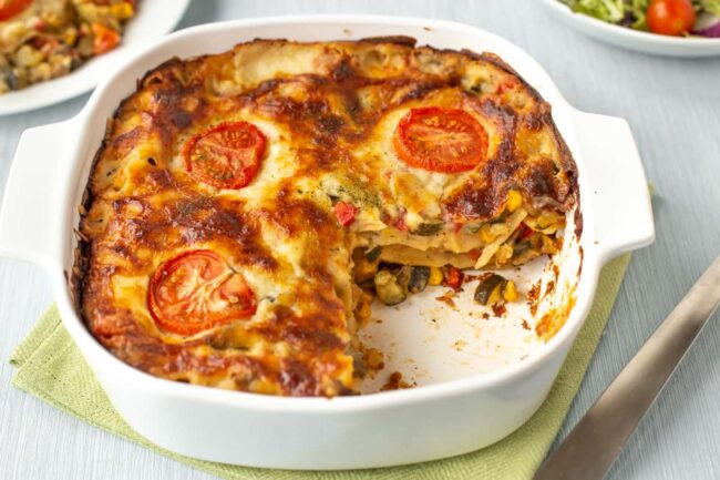 A crispy vegetable lasagne in a baking dish, with a slice removed so you can see the layers.