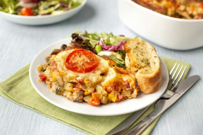 A portion of vegetable lasagne on a plate with garlic bread and salad.