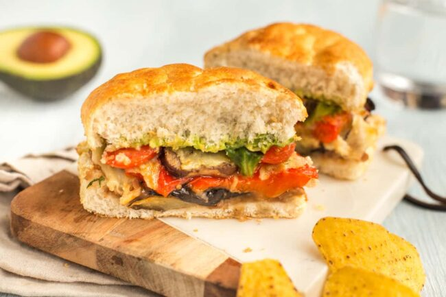 A Mexican sandwich cut in half, showing cheesy roasted vegetables and avocado.