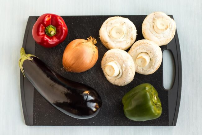 A selection of Mediterranean vegetables on a black chopping board.