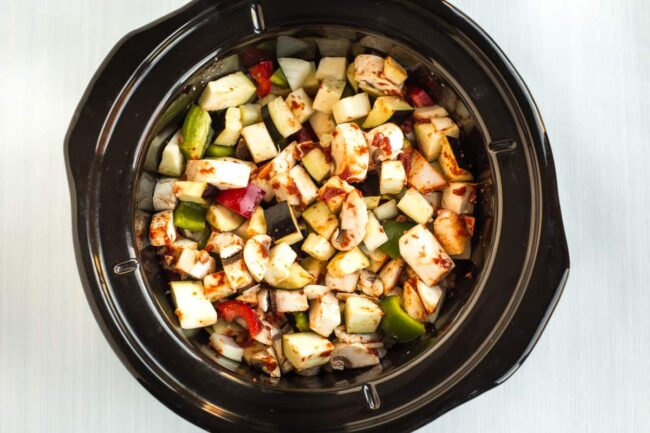 Chopped Mediterranean vegetables in a slow cooker pot.