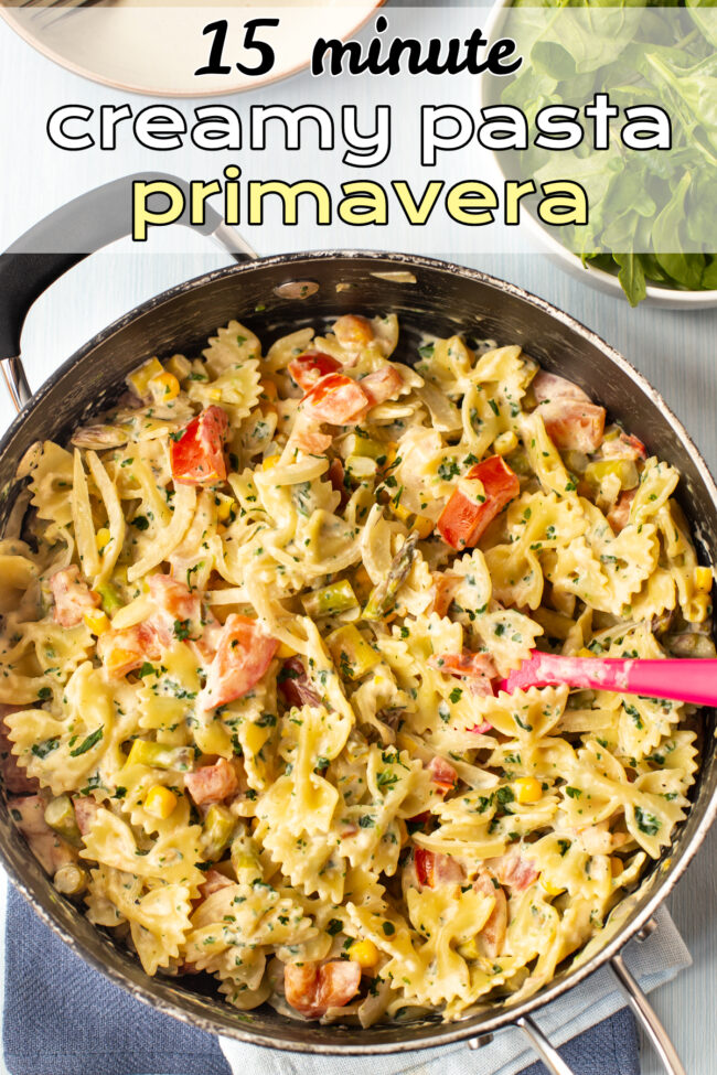 Pasta primavera with vegetables and a creamy sauce in a pan.