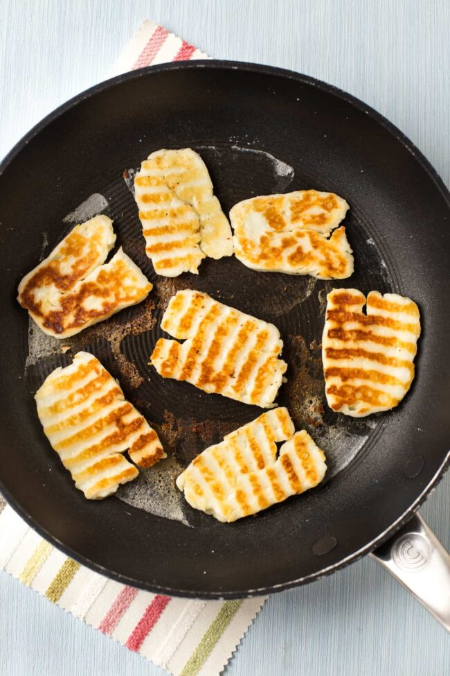 Slices of crispy halloumi cheese with golden brown griddle marks.