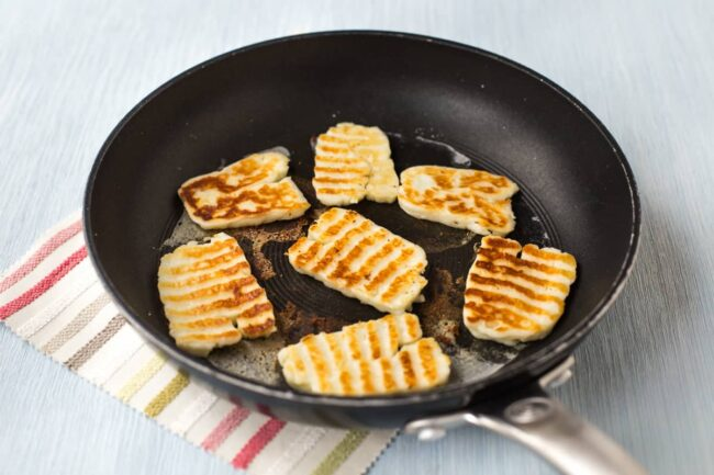 Halloumi cheese with grill lines in a frying pan.