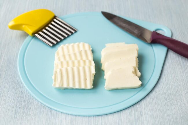 Halloumi cheese cut with a knife, and with a crinkle cutter.