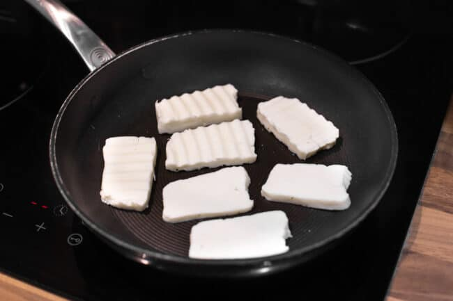 Slices of uncooked halloumi in a frying pan.