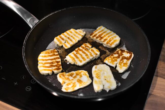 Crispy slices of halloumi cheese in a frying pan.