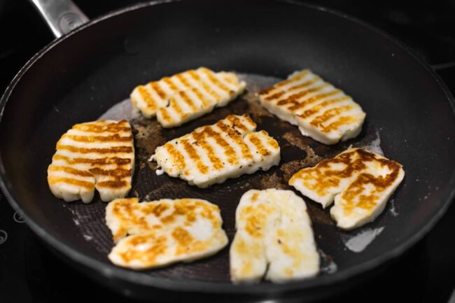 Slices of halloumi cheese with golden grill lines.