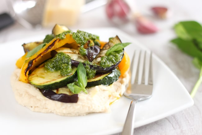 White bean mash with griddled courgette, peppers and aubergine and homemade pesto, served on a plate with a fork