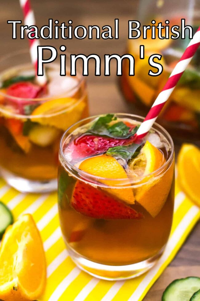 A glass of Pimm's with oranges, strawberries and mint, served with a stripey straw.