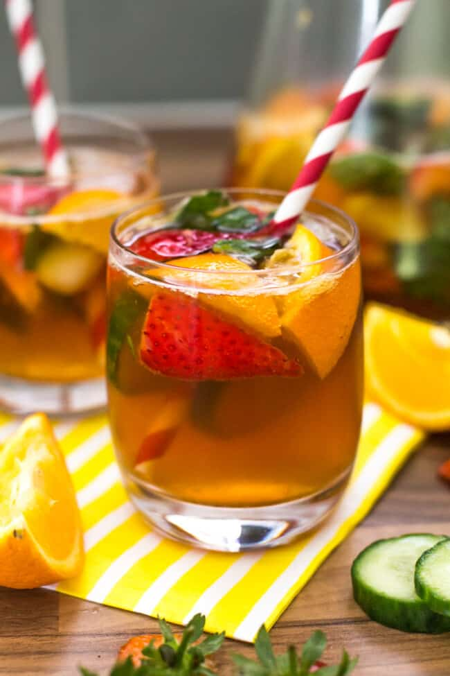 A small glass of Pimm's with strawberries, cucumber and oranges.