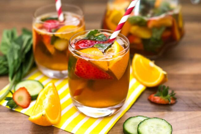 A glass of Pimm's with fresh fruit and a straw.