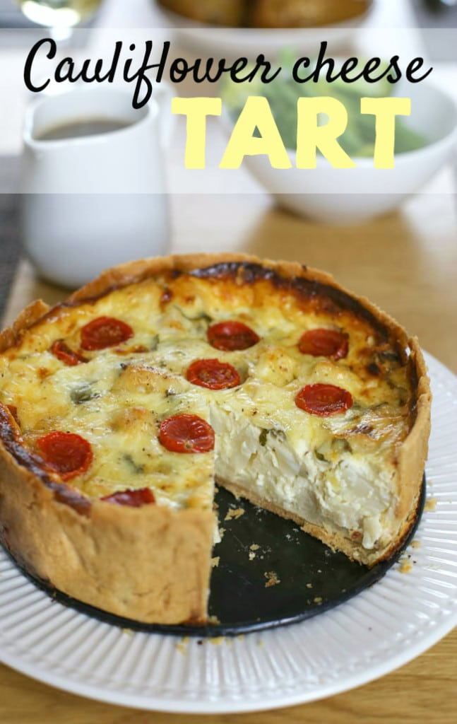 Cauliflower cheese tart - this irresistible tart combines a light and cheesy filling with juicy roasted tomatoes and flaky shortcrust pastry. A dreamy dinner party treat!