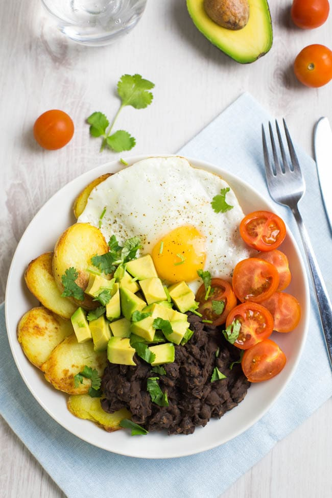 Smoky black bean breakfast bowls! Spicy chipotle black beans, served with crispy potatoes, a fried egg, and lots of fresh veggies - a brilliant way to start the day! Vegetarian, gluten-free, and easily made vegan.