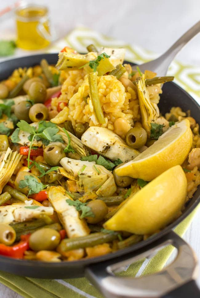 This Spanish vegetarian paella recipe is really easy and straightforward to make, and is packed with veggies! The artichokes and olives are the star of the show for me. Finish it off with some extra virgin olive oil, lemon juice and parsley for a comforting vegan dinner that tastes fresh and summery too!