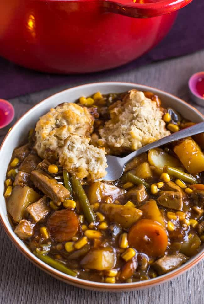Vegetarian 'beef' stew in a rich gravy, topped with easy suet dumplings - an old recipe from an authentic British mum! Such a brilliant winter warmer.