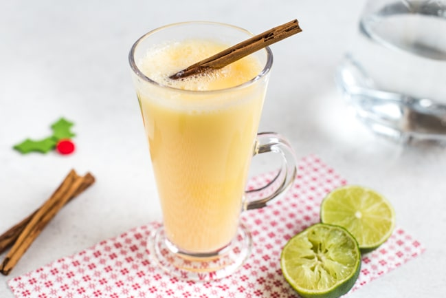 A snowball cocktail in a glass mug with a cinnamon stick