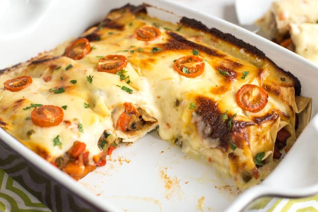 Refried bean enchiladas with jalapeno cheese sauce in a baking dish with a piece removed