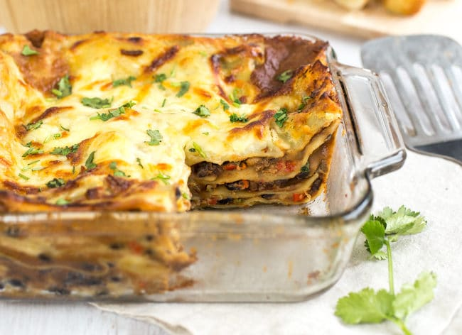 Mexican vegetarian lasagne in a baking dish with a slice removed