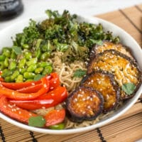 Roasted edamame noodle bowls with miso roasted aubergine and crispy kale