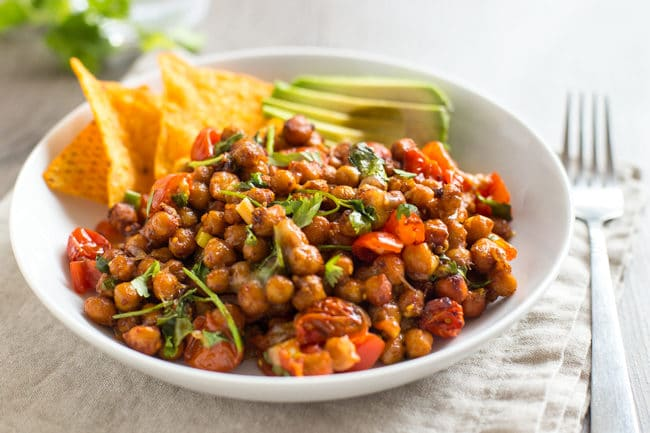 Nacho roasted chickpeas in a bowl with tortilla chips and avocado