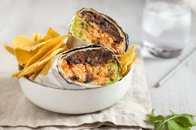 BBQ bean burritos wrapped in foil, served in a bowl with tortilla chips